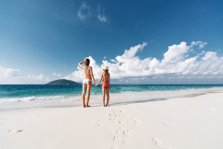 beach sun: Mother with her 8 years old daughter resting on a tropical beach during summer vacations Stock Photo