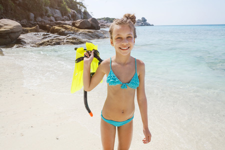 kids playing beach: Preteen child posing with snorkeling equipment on a tropical beach