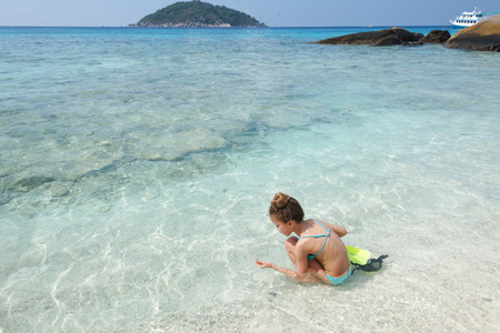 Child playing in clear sea water on a tropical beach photo