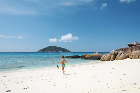 Preteen child are going snorkeling on a tropical beach photo