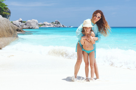 Mother with her 8 years old daughter on a tropical beach during summer vacations