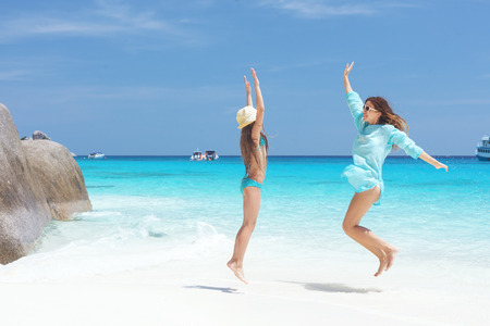 8 years old: Mother with her 8 years old daughter jumping on a tropical beach during summer vacations