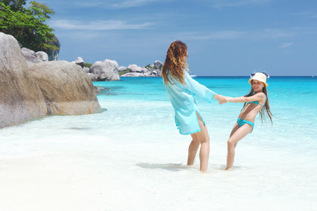 nine years old: Mother playing with her 8 years old daughter on a tropical beach during summer vacations