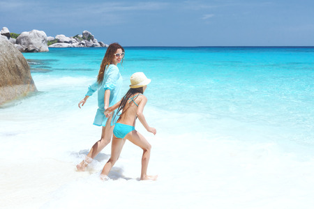 preteens beach: Mother with her 8 years old daughter resting on a tropical beach during summer vacations Stock Photo