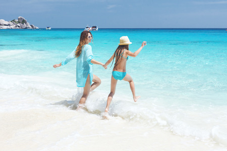 8 years old: Mother with her 8 years old daughter resting on a tropical beach during summer vacations Stock Photo