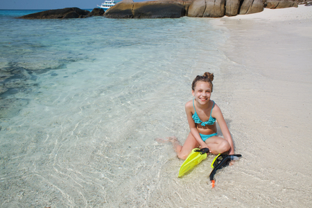 preteens girl: Preteen child posing with snorkeling equipment on a tropical beach
