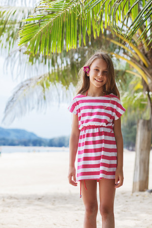 8 years old girl resting on the tropical palm beach in Thailand in summer Фото со стока