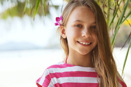 8 years old girl resting on the tropical palm beach in Thailand in summer, holding orchid flower in her hair, portrait close up