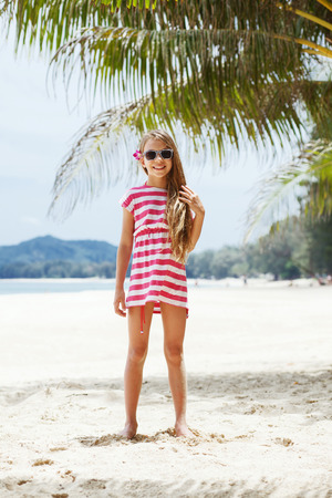 8 years old girl resting on the tropical palm beach in Thailand in summer Stock Photo