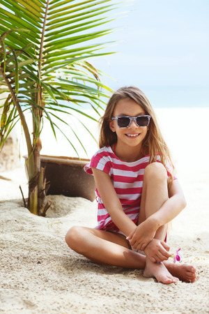 beautiful preteen girl: 8 years old girl resting on the tropical palm beach in Thailand in summer Stock Photo
