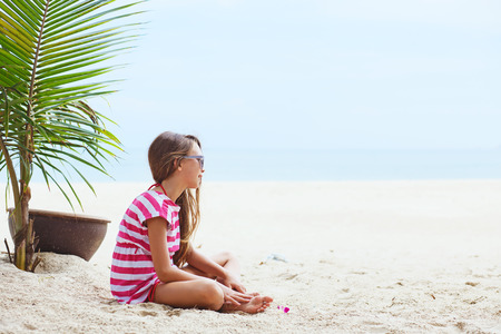 beach sun: 8 years old girl resting on the tropical palm beach in Thailand in summer Stock Photo