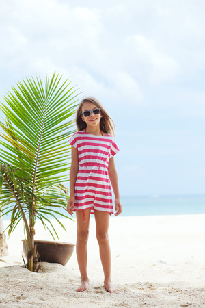 beach wear: 8 years old girl resting on the tropical palm beach in Thailand in summer Stock Photo