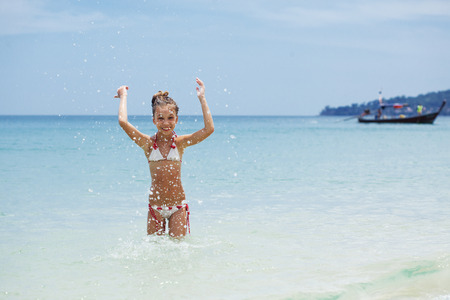 Child playing in sea water on a tropical beach during summer vacations Stock Photo