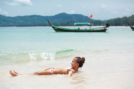 nine years old: Child playing in sea water on a tropical beach during summer vacations Stock Photo