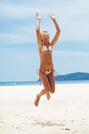 Child jumping on a tropical beach during summer vacations Stock Photo