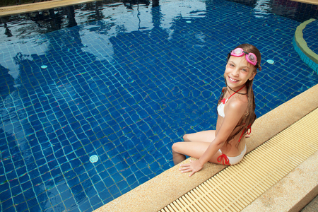 8 years: 8 years old girl playing in swimming pool at hotel