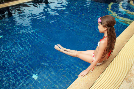 pool preteen: 8 years old girl playing in swimming pool at hotel