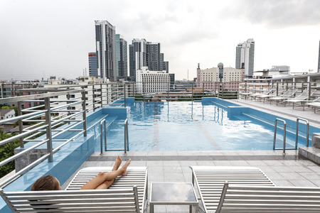 Girl relaxing in the pool on the roof of resort with urban view on skyscraper in Bangkok city Stock Photo