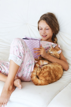 modern girls: Preteen school girl of 8-9 years old playing on tablet pc and hugging her cat resting on a sofa at home Stock Photo