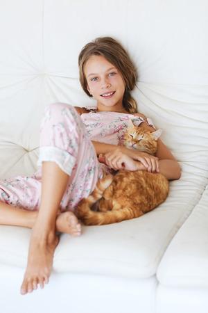 gato jugando: Niña de la escuela del preadolescente de 8-9 años de edad con su mascota descansando en un sofá en casa
