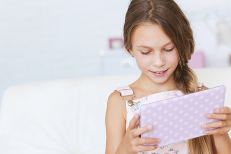 modern girls: Preteen school girl of 8-9 years old playing on tablet pc at home