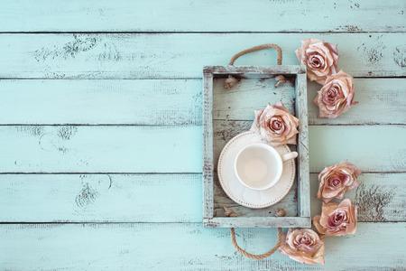 磁器の茶碗とぼろぼろのシックなミントの背景、トップ ビュー ポイントにバラの芽とヴィンテージの木製トレイ