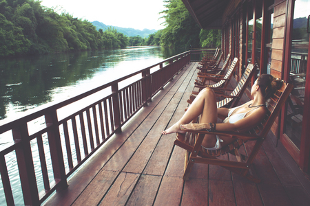 Woman relaxing in wooden chair in floating hotel on the River Kwai in Thailand
