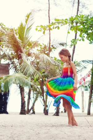 preteens girl: 8 years old girl wearing colorful rainbow dress resting on the tropical palm beach in Thailand in summer