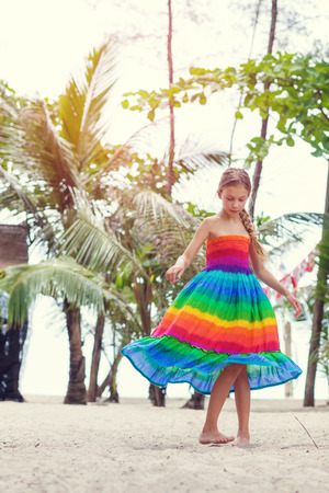 beach clothes: 8 years old girl wearing colorful rainbow dress resting on the tropical palm beach in Thailand in summer