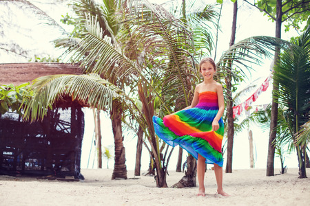 8 years old: 8 years old girl wearing colorful rainbow dress resting on the tropical palm beach in Thailand in summer