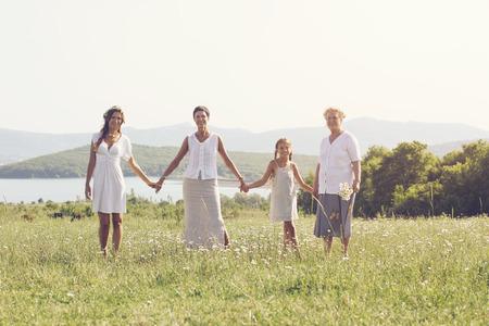 カモミール フィールドで一緒と笑みを浮かべて立っている美しい女性の 4 つの世代