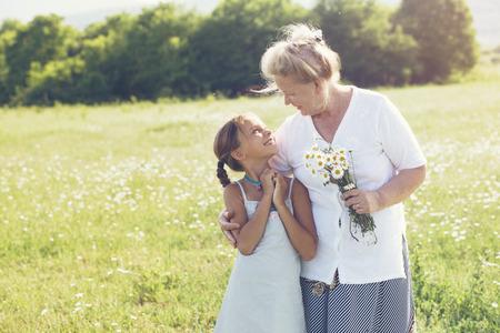 an elderly person: Gran-abuela y nieta de pie en el campo de flores en la luz del sol