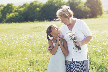 elderly: Great-grandmother and granddaughter standing in flower field in sunlight