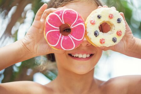 comiendo: Chica chico lindo que come rosquillas dulces Foto de archivo