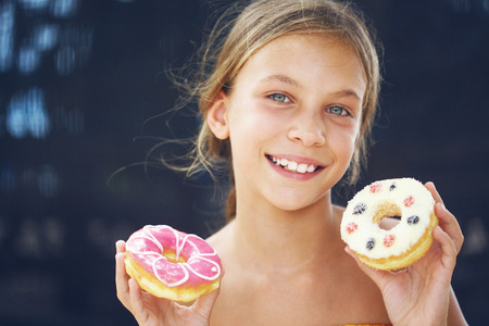 hungry kid: Cute kid girl eating sweet donuts