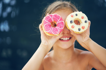 hungry children: Cute kid girl eating sweet donuts