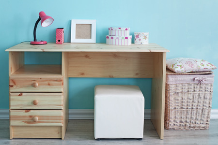 a study: Interior detail. Study table and decor for kid girl in bedroom over blue wall Stock Photo