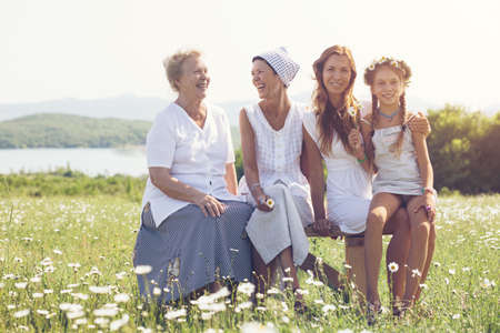 4 years old: Four generations of beautiful women sitting together in a camomile field and smiling