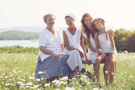 čtyři lidé: Čtyři generace krásných žen spolu seděli v heřmánku pole a usměvavý Reklamní fotografie