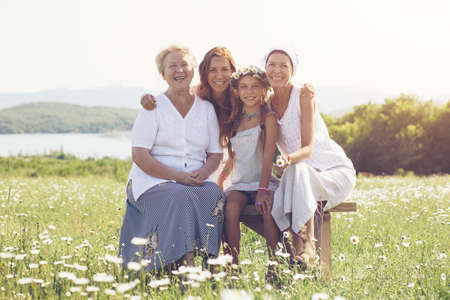 multi generation: Four generations of beautiful women sitting together in a camomile field and smiling