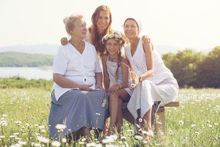 Quatro gerações de mulheres bonitas sentam-se junto em um campo da camomila e sorrindo