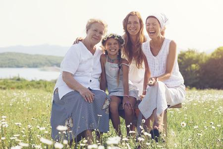 Vier generaties van mooie vrouwen bij elkaar zitten in een kamille veld en glimlachen