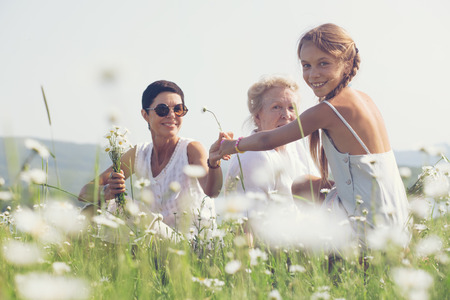 Three generations of beautiful women sitting together in a camomile field and smiling Stock Photo