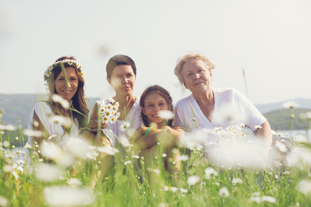 Four generations of beautiful women sitting together in a camomile field and smiling photo