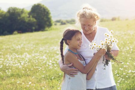 Groot-grootmoeder en kleindochter staan in bloem veld in zonlicht Stockfoto