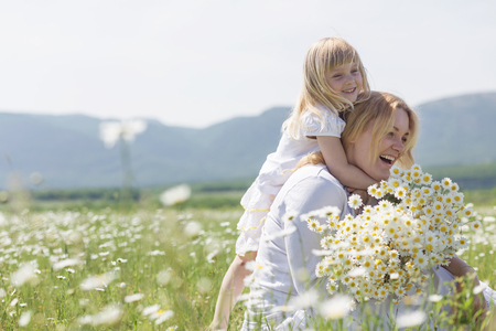 emotional freedom: Happy mother playing with her daughter in flower field Stock Photo