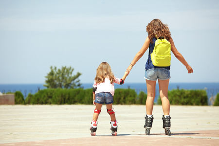 rollerskating: Young mother with her 5 years old daughter rollerskating in park, rear view