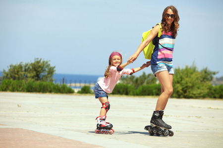 Young mother with her 5 years old daughter rollerskating in park Фото со стока