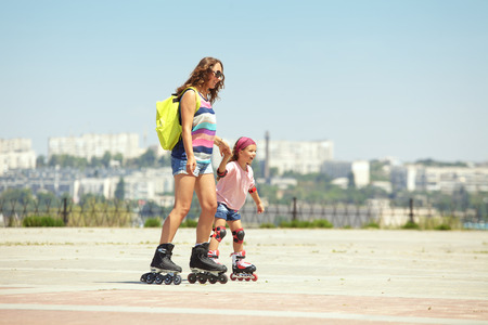 rollerskating: Young mother with her 5 years old daughter rollerskating in park Stock Photo