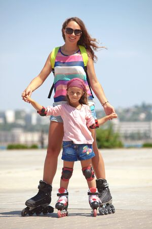 5 years old: Young mother with her 5 years old daughter rollerskating in park Stock Photo